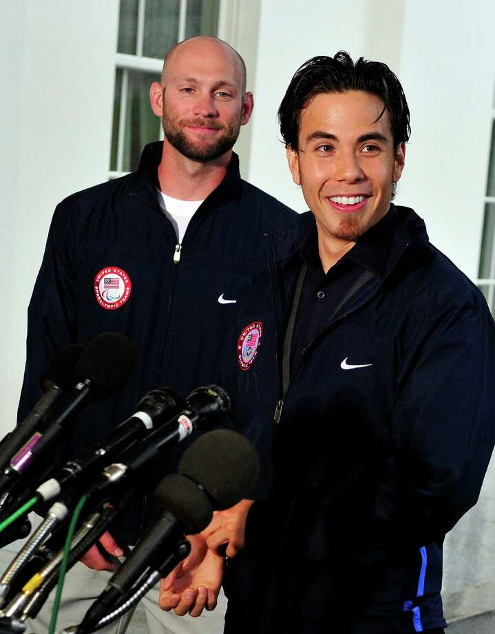 Apolo Anton Ohno makes remarks to reporters as Heath Calhoun, Paralympic Sit Skiier, left, looks on, after meeting United States President Barack Obama and first lady Michele Obama at the White House on April 21, 2010 in Washington, DC. Photo: Pool, Getty Images / 2010 Getty Images