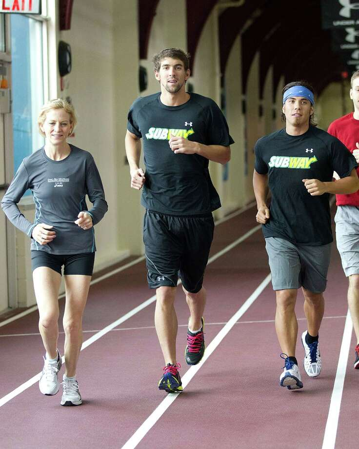Mary Wittenberg, Michael Phelps, and Apolo Anton Ohno run during the ING NYC Marathon training session at Chelsea Piers Sports Center on Sept. 27, 2011 in New York City. Photo: Dario Cantatore, Getty Images / 2011 Dario Cantatore