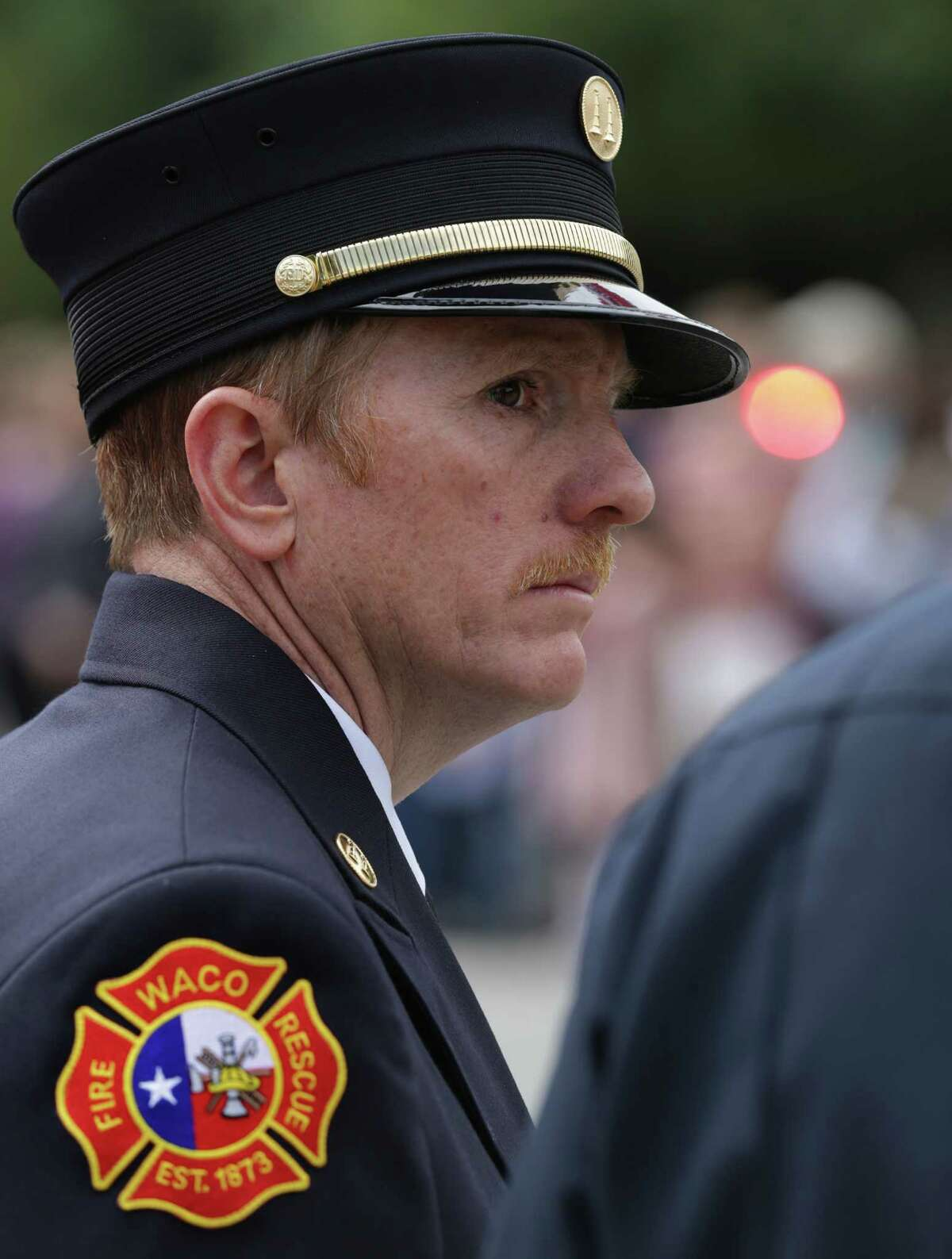 Robert Beechner of the Waco Fire Department watches as the procession goes by on Thursday April 25, 2013 at the Ferrell Center at Baylor University, where President Obama is scheduled to speak, honoring the first responders that were killed in the blast in West, TX.