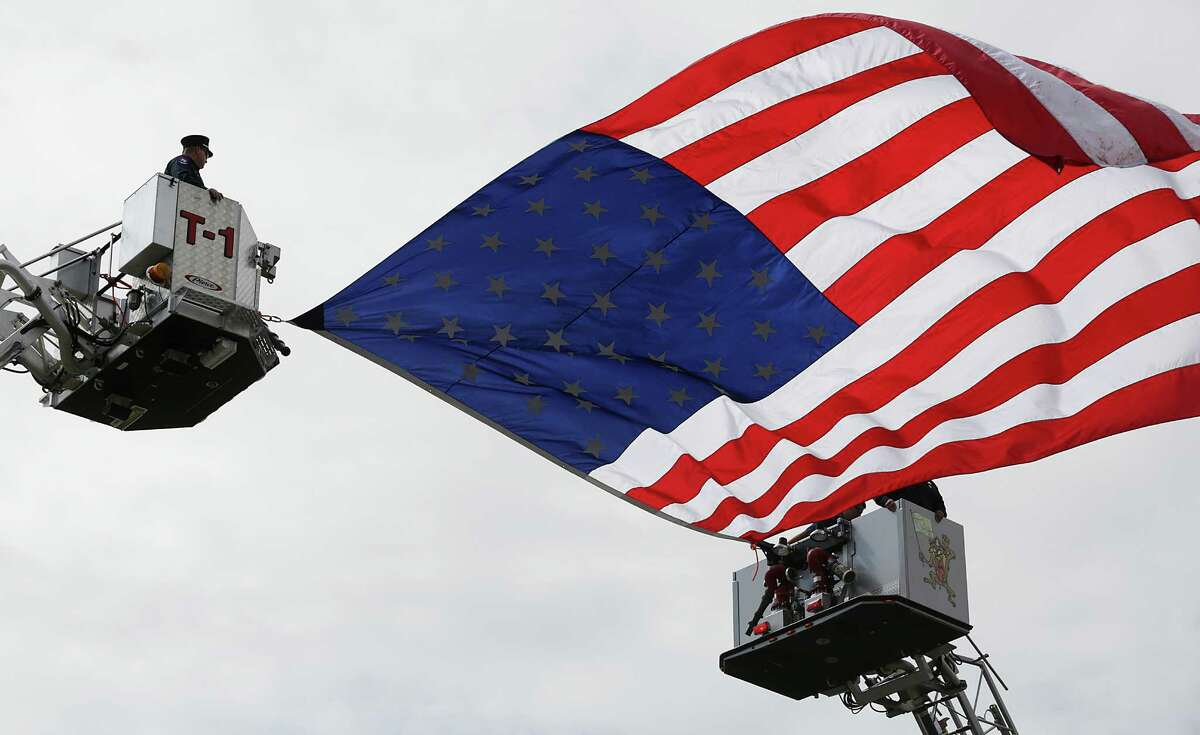 Members of the Waco Fire Department Honor Guard fly an American flag between trucks on Thursday April 25, 2013 at the Ferrell Center at Baylor University, where President Obama is scheduled to speak honoring the fallen firefighters that were killed the blast in West, TX.
