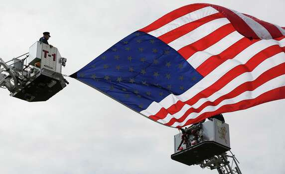 Members of the Waco Fire Department Honor Guard fly an American flag between trucks on Thursday April 25, 2013 at the Ferrell Center at Baylor University, where President Obama is scheduled to speak honoring the fallen firefighters that were killed the blast in West, TX. Photo: Bob Owen, San Antonio Express-News / ©2013 San Antonio Express-News