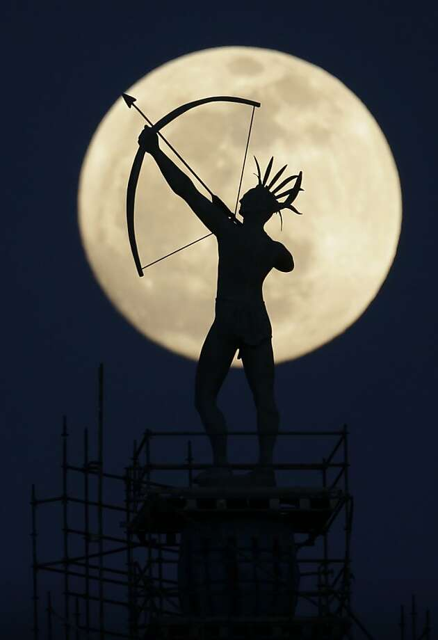 Shooting the moon: The Kansa Indian bowman on top of the Kansas Statehouse in Topeka is silhouetted by a rising moon. Photo: Charlie Riedel, Associated Press