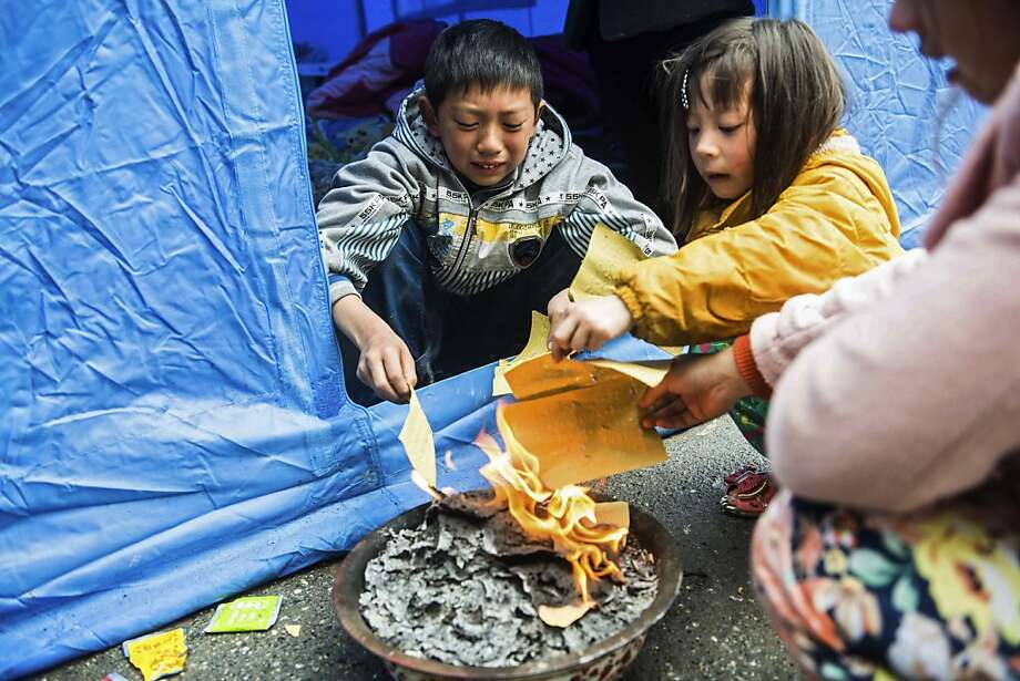 Desperate times: The wife and children of Huang Zongxue, who died in Saturday's earthquake in Ya'an, Sichuan province, burn paper to stay warm. The Chinese quake killed at least 193 people, injured more than 12,000 and left tens of thousands of homeless survivors living in makeshift tents or in the streets. Photo: Afp, AFP/Getty Images