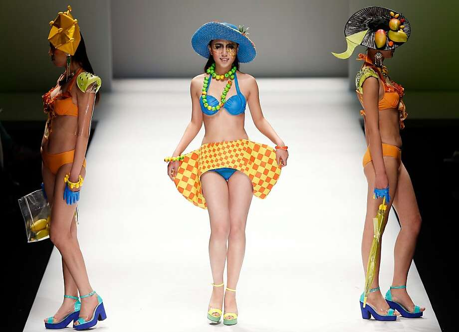 Let's see - bikinis, purple heels, fruit hat, finger gloves, shoulder armor -yup, we're ready for the beach! Models strut down the catwalk of the Hebei University College of Textiles and Garments show in Beijing. Photo: Lintao Zhang, Getty Images