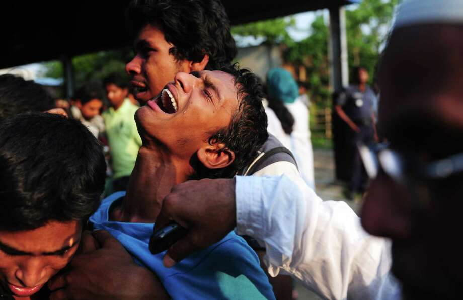 TOPSHOTS A Bangladeshi youth reacts after seeing his relatives dead body after a building collapse in Savar, on the outskirts of Dhaka, on April 24, 2013. An eight-storey building containing several garment factories collapsed in Bangladesh, killing at least 82 people and further highlighting safety problems in the clothing industry.  Armed with concrete cutters and cranes, hundreds of fire service and army rescue workers struggled to find survivors in the mountain of concrete and mangled steel, which resembled the aftermath of an earthquake. AFP PHOTO/ Munir uz ZAMANMUNIR UZ ZAMAN/AFP/Getty Images Photo: MUNIR UZ ZAMAN, AFP/Getty Images / AFP
