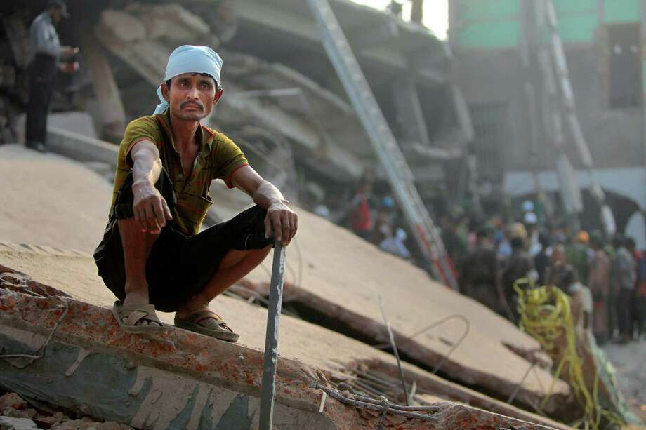 A Bangladeshi rescue worker takes a break at the site of a building that collapsed Wednesday in Savar, near Dhaka, Bangladesh,Thursday, April 25, 2013. By Thursday, the death toll reached at least 194 people as rescuers continued to search for injured and missing, after a huge section of an eight-story building that housed several garment factories splintered into a pile of concrete. Photo: A.M. Ahad, AP / AP