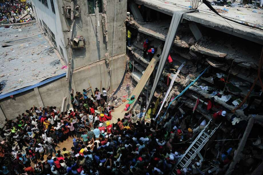 TOPSHOTS Volunteers use a length of textile as a slide to move dead victims recovered from the rubble after an eight-storey building collapsed in Savar, on the outskirts of Dhaka, on April 25, 2013. The death toll in the Bangladesh's worst industrial disaster reached 200 people after rescue workers pulled out scores more corpses from the rubble of a collapsed garment factory building. AFP PHOTO/Munir uz ZAMANMUNIR UZ ZAMAN/AFP/Getty Images Photo: MUNIR UZ ZAMAN, AFP/Getty Images / AFP