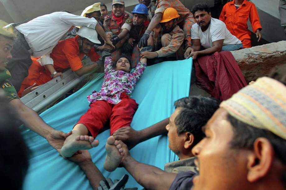 Rescuers lower down a survivor from the debris of a building that collapsed in Savar, near Dhaka, Bangladesh, Wednesday, April 24, 2013. An eight-storey building housing several garment factories collapsed near Bangladesh's capital on Wednesday, killing dozens of people and trapping many more under a jumbled mess of concrete. Rescuers tried to cut through the debris with earthmovers, drilling machines and their bare hands. Photo: A.M. Ahad, AP / AP