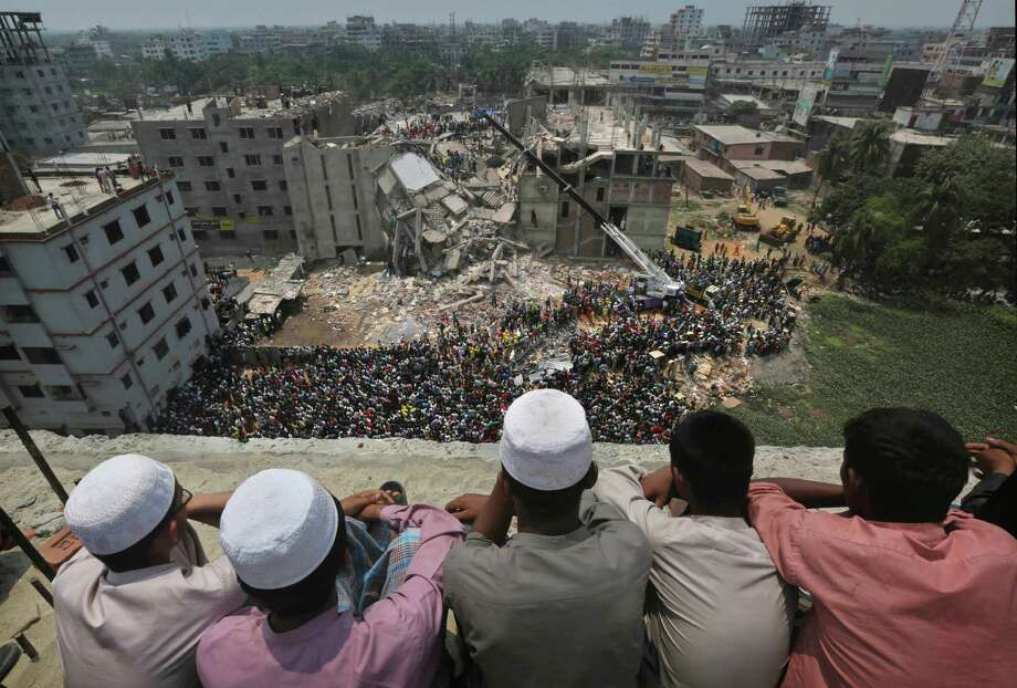 Bangladeshi boys watch the rescue operations from a rooftop at the site of a building that collapsed Wednesday in Savar, near Dhaka, Bangladesh, Thursday, April 25, 2013. By Thursday, the death toll reached at least 194 people as rescuers continued to search for injured and missing, after a huge section of an eight-story building that housed several garment factories splintered into a pile of concrete. Photo: Kevin Frayer, AP / AP