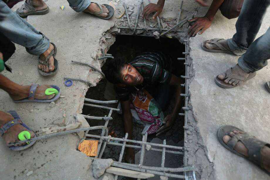 A Bangladeshi rescuer looks out from a hole cut in the concrete at the site of a building that collapsed Wednesday in Savar, near Dhaka, Bangladesh, Thursday, April 25, 2013. By Thursday, the death toll reached at least 194 people as rescuers continued to search for injured and missing, after a huge section of an eight-story building that housed several garment factories splintered into a pile of concrete. Photo: Kevin Frayer, AP / AP