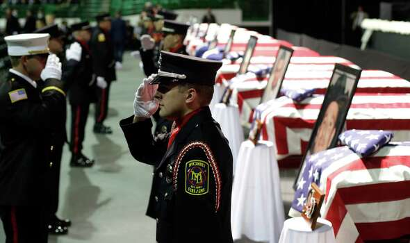 Honor guard salute as they change shift prior to a memorial service for first responders who died in last week's fertilizer plant explosion in West, Texas, Thursday, April 25, 2013, in Waco, Texas.  President Barack Obama, U.S. Sen. John Cornyn and Texas Gov. Rick Perry are set to speak at Thursday's memorial at Baylor University's Ferrell Center in Waco. Firefighters and other first responders were among those killed when a fire at the plant erupted in an explosion last week. Hundreds of people were injured. (AP Photo/Eric Gay) Photo: Eric Gay, Associated Press / AP