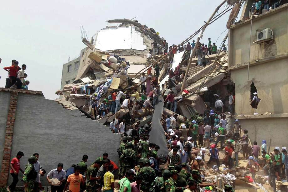 Rescue workers and people look for survivors after an eight-story building housing several garment factories collapsed in Savar, near Dhaka, Bangladesh, Wednesday, April 24, 2013. Dozens were killed and many more are feared trapped in the rubble. Photo: A.M. Ahad, AP / AP