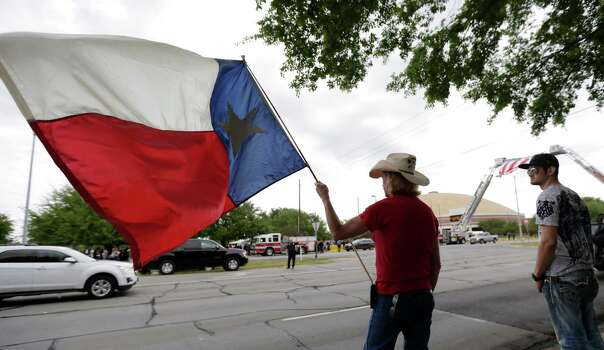 Mark Turner holds a Texas flag as he wait for a procession to pass prior to a memorial service for first responders who died in last week's fertilizer plant explosion in West, Texas, Thursday, April 25, 2013, in Waco, Texas.  President Barack Obama, U.S. Sen. John Cornyn and Texas Gov. Rick Perry are set to speak at Thursday's memorial at Baylor University's Ferrell Center in Waco. Firefighters and other first responders were among those killed when a fire at the plant erupted in an explosion last week. Hundreds of people were injured. (AP Photo/Eric Gay) Photo: Eric Gay, Associated Press / AP
