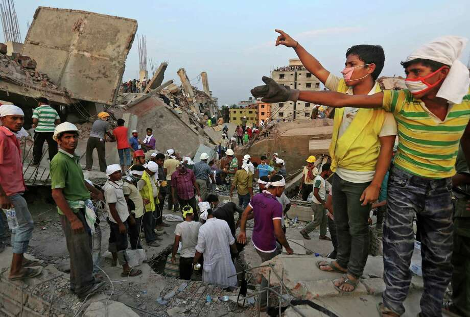 Bangladeshi rescuers from a youth group gesture for help at the site of a building that collapsed Wednesday in Savar, near Dhaka, Bangladesh, Thursday, April 25, 2013. By Thursday, the death toll reached at least 194 people as rescuers continued to search for injured and missing, after a huge section of an eight-story building that housed several garment factories splintered into a pile of concrete. Photo: Kevin Frayer, AP / AP