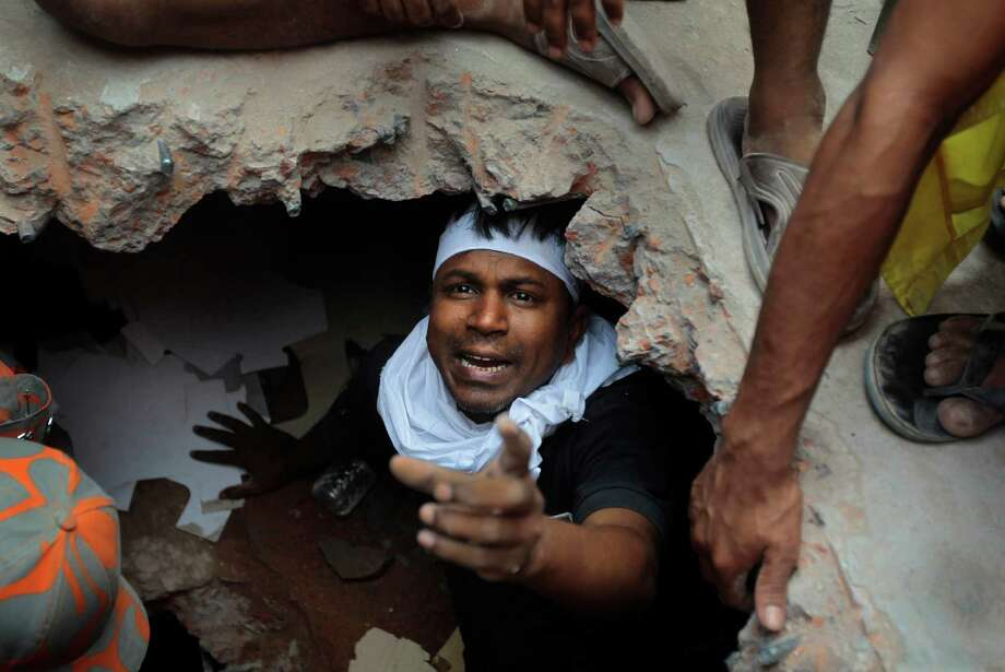 A Bangladeshi rescuer looking for survivors gestures from beneath a concrete slab of a building that collapsed  Wednesday in Savar, near Dhaka, Bangladesh,Thursday, April 25, 2013. By Thursday, the death toll reached at least 194 people as rescuers continued to search for injured and missing, after a huge section of an eight-story building that housed several garment factories splintered into a pile of concrete. Photo: A.M. Ahad, AP / AP