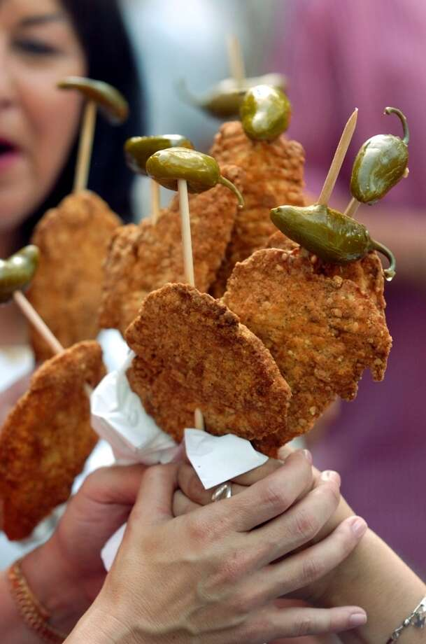Chicken on a stick can be found at a number of Fiesta events, but there's something about the ones at Oyster Bake. Must be ordered with jalapenos, of course.Winner: Tie - The State Fair's fried Thanksgiving dinner is practically a complete meal, but how do you eat it while walking around with a beer in hand? A stick might help.