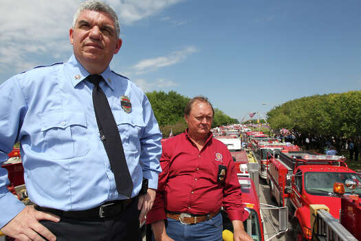 Mike Bluff (left) and Jerry Pavelka watch from atop a truck as firefighters congregate at Baylor University for memorial services for their fallen comrades in West  on  April 25 2013. Photo: TOM REEL