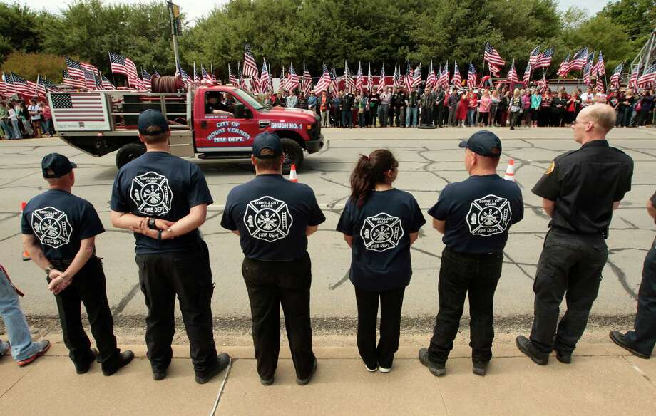 WACO, TX - APRIL 25:   Members of the Corvell City and Osage Volunteer Fire Department watch as fire departments from around Texas pay their respects during a parade for the West Memorial Service on April 25, 2013 in Waco, Texas. The memorial service honored the volunteer firefighters that lost their lives at the fertilizer plant explosion in West, Texas last week. Photo: Erich Schlegel, Getty Images / 2013 Getty Images