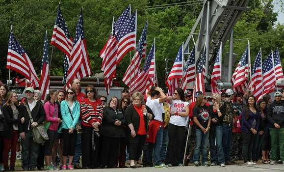 WACO, TX - APRIL 25:  People stand in front of American flags as fire departments from around Texas pay their respects during a parade for the West Memorial Service on April 25, 2013 in Waco, Texas. The memorial service honored the volunteer firefighters that lost their lives at the fertilizer plant explosion in West, Texas last week. Photo: Erich Schlegel, Getty Images / 2013 Getty Images