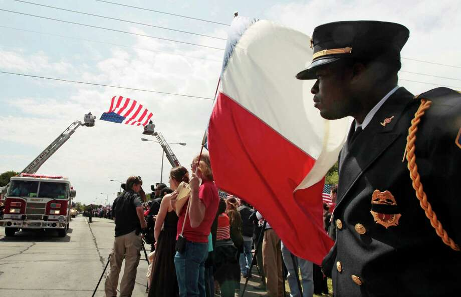 WACO, TX - APRIL 25: T yrell Hobbs of the Groesbeck Volunteer Fire Department stands watches as fire departments from around Texas pay their respects during a parade for the West Memorial Service on April 25, 2013 in Waco, Texas. The memorial service honored the volunteer firefighters that lost their lives at the fertilizer plant explosion in West, Texas last week. Photo: Erich Schlegel, Getty Images / 2013 Getty Images