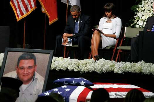 President Barack Obama and first lady Michelle Obama bow their heads behind a photo of volunteer firefighter Capt. Cyrus Adam Reed, who was killed, as they attend the memorial for victims of the fertilizer plant explosion in West, Texas, Thursday, April 25, 2013, at Baylor University in Waco,Texas. (AP Photo/Charles Dharapak) Photo: Charles Dharapak, Associated Press / AP
