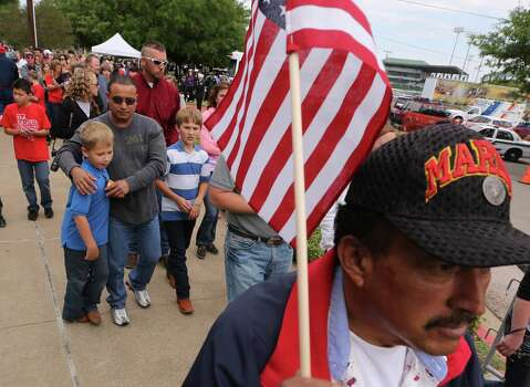 Gulf war veteran Celso Castro, right carries an flag while heading to a memorial service for first responders who died in last week's fertilizer plant explosion in West, Texas, Thursday, April 25, 2013, in Waco, Texas.  President Barack Obama, U.S. Sen. John Cornyn and Texas Gov. Rick Perry are set to speak at Thursday's memorial at Baylor University's Ferrell Center in Waco. (AP Photo/Waco Tribune Herald, Rod Aydelotte) Photo: Rod Aydelotte, Associated Press / The Waco Tribune-Herald
