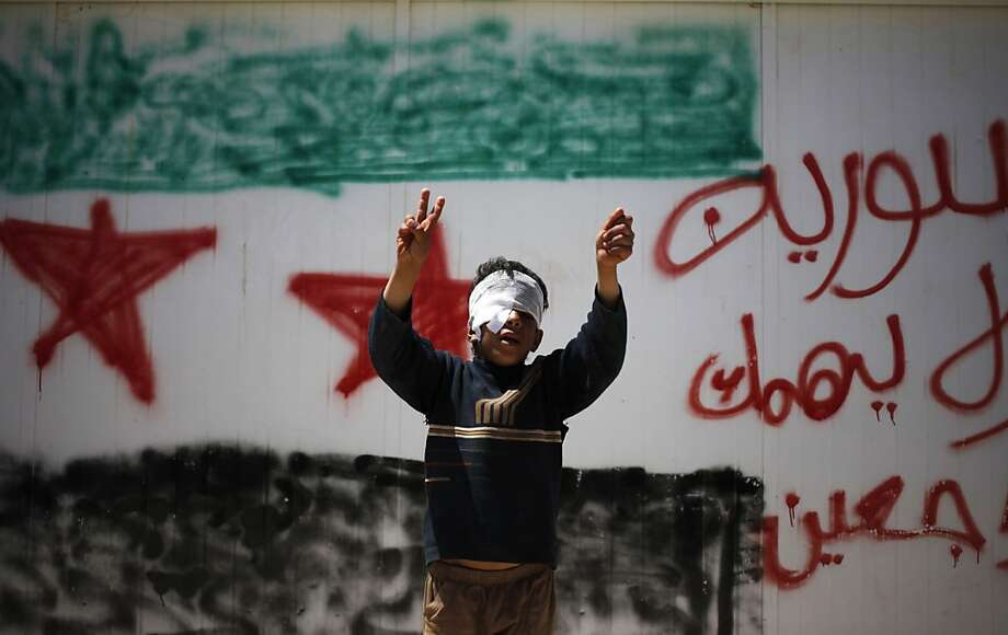 "Syrian refugee Bashar al-Zalfi, 10, waves the victory sign while posing in front of a wall with the colors of the revolutionary flag, and Arabic reading, ""Syria, don't worry, we will return,"" at Zaatari refugee camp, in Mafraq, Jordan, Thursday, April 25, 2013. Bashar was injured with his right eye in Daraa, Syria during a bombing by the government Syrian forces. Photo: Mohammad Hannon, Associated Press"