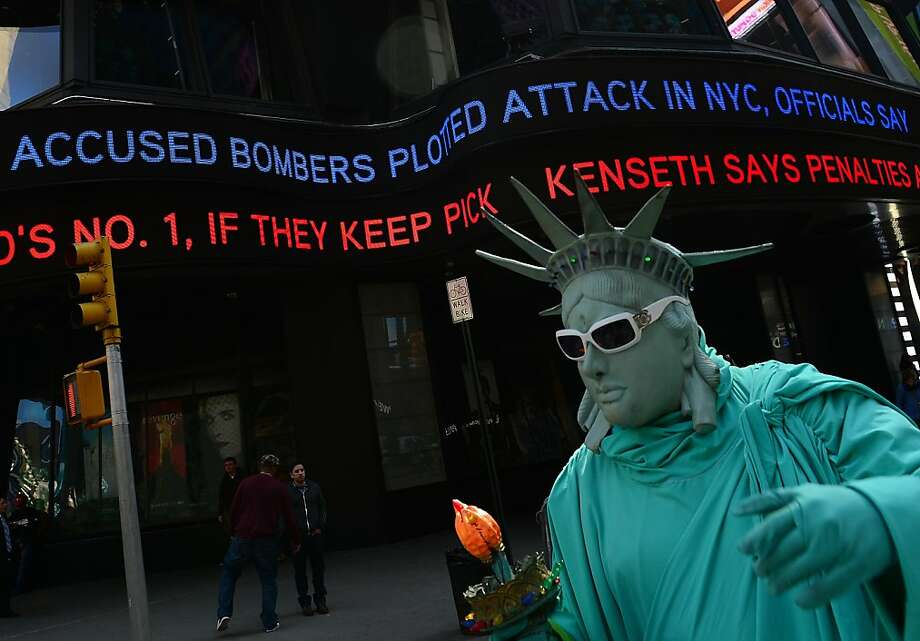 As a street performer acts as the Statue of Liberty, a news ticker announces on April 25, 2013, that the bombers in the Boston Marathon were plotting attacks on New York City's Times Square in New York.  Photo: Emmanuel Dunand, AFP/Getty Images