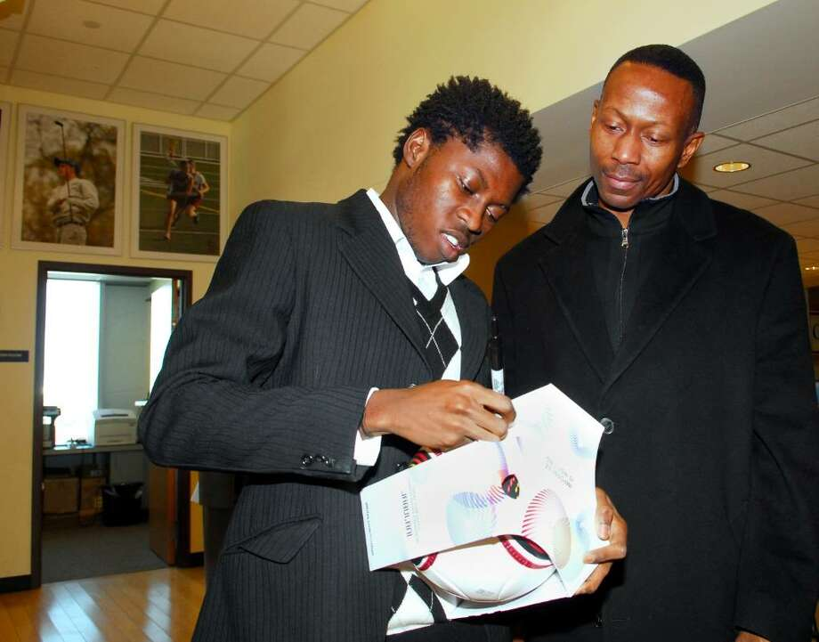 St. Luke's soccer player, Kofi Agyapong, a native of Ghana, left, signs a soccer ball for Serge Reiph (a parent of a St. Luke's student), during a ceremonial signing at St. Luke's in where it was announced that Agyapong will attend Wake Forest University in North Carolina to play soccer. Photo: Bob Luckey / Stamford Advocate