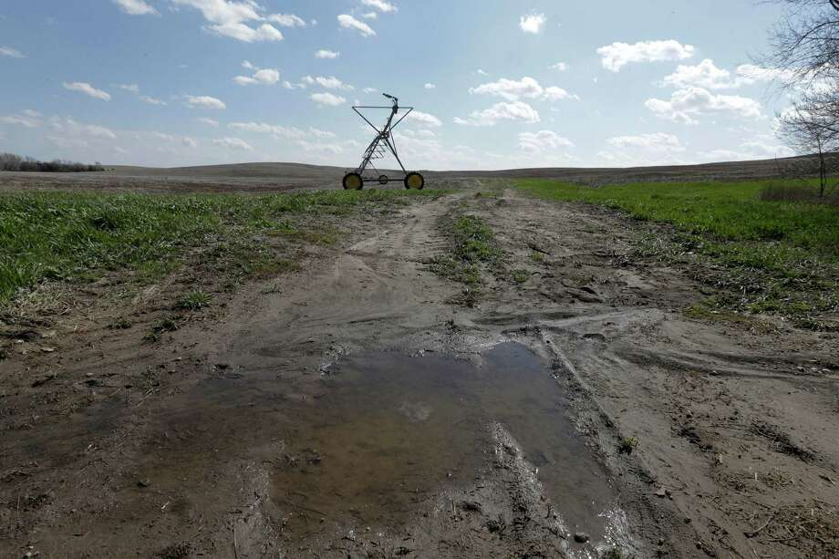 Farmers who have spent the past several months staring at parched fields have a new problem: mud, as rain water pools gather in fields. Photo: Nati Harnik, STF / AP