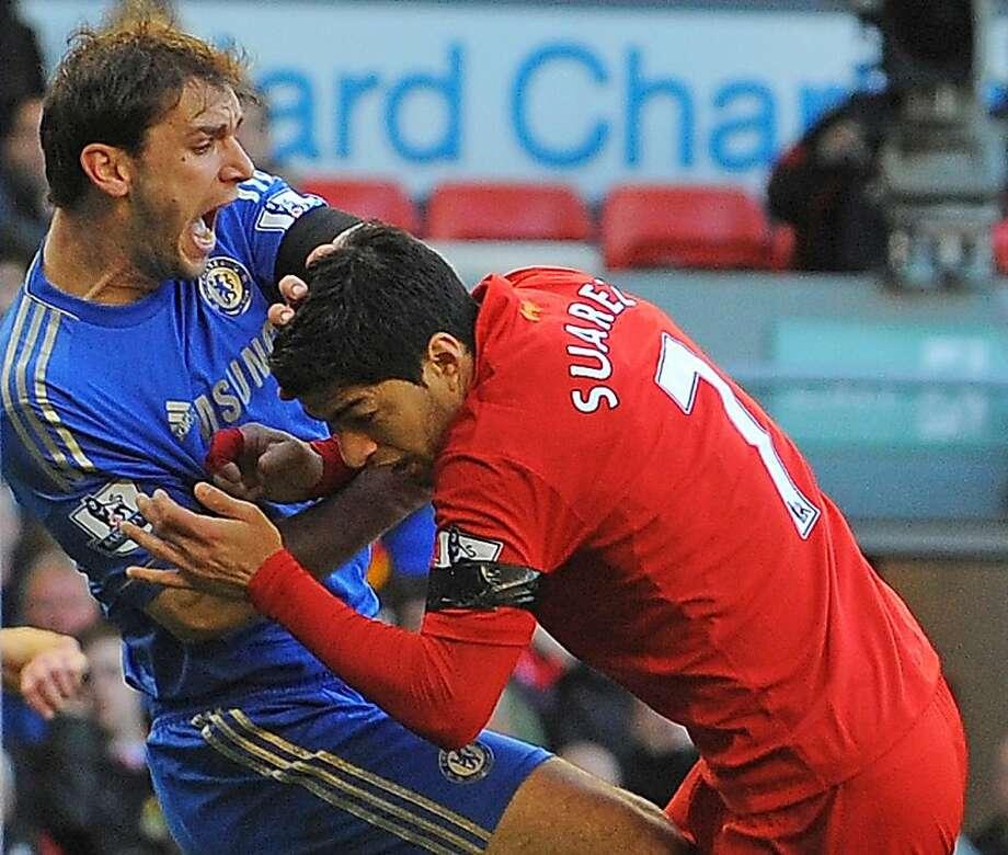 Chelsea's Branislav Ivanovic (left) feels the pain of Luis Suarez's bite. Photo: Andrew Yates, AFP/Getty Images