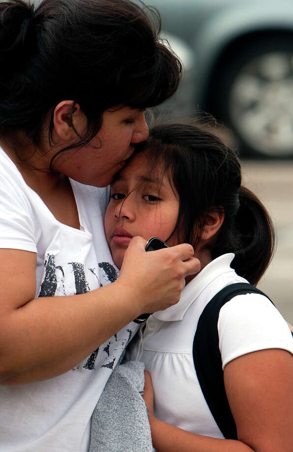 A woman comforts a child after the girl leaves an Alief ISD school bus that collided with a car along Briarpark near Westoffice on Thursday. Photo: Cody Duty, Houston Chronicle / © 2013 Houston Chronicle