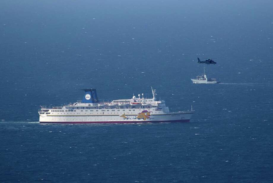 An Israeli military naval ship and an Israeli air force helicopter operate next to a cruise ship off the coast of Haifa, northern Israel, Thursday. Photo: Ariel Schalit, STF / AP