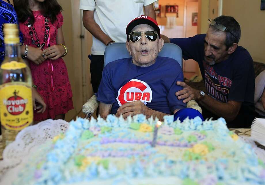 Former Washington Senators pitcher Connie Marrero is surrounded by family and friends in Havana on Thursday as he blows out the candles on the cake marking his 102nd birthday. Photo: Franklin Reyes, Associated Press