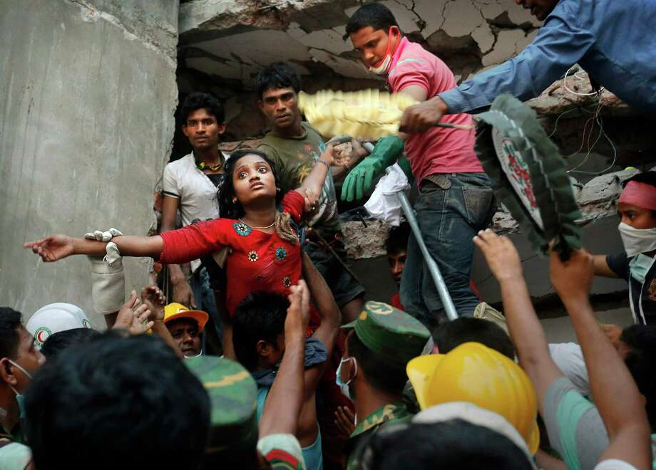A Bangladeshi woman survivor is lifted out of the rubble by rescuers at the site of a building that collapsed Wednesday in Savar, near Dhaka, Bangladesh, Thursday, April 25, 2013. By Thursday, the death toll reached at least 194 people as rescuers continued to search for injured and missing, after a huge section of an eight-story building that housed several garment factories splintered into a pile of concrete.(AP Photo/Kevin Frayer) Photo: Kevin Frayer, STF / AP