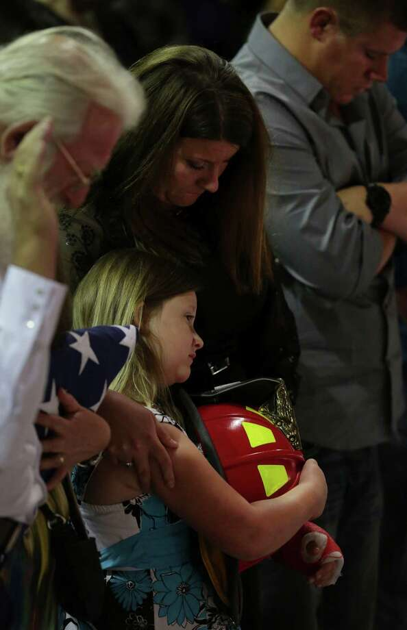 A young girl, comforted by her mother, holds the helmet of one of the 12 fallen first responders, on Thursday, April 25, 2013, during the memorial service for the firefighters killed in the West explosion. Photo: Bob Owen, San Antonio Express-News / ©2013 San Antonio Express-News