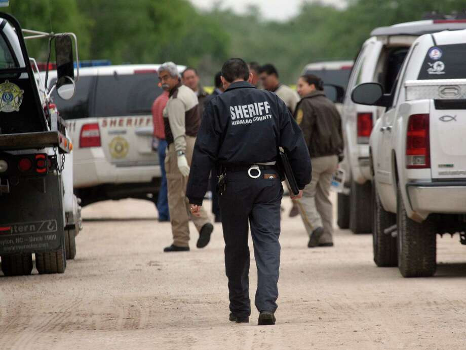 "Hidalgo County sheriff investigators converge on the scene on N. Bryan road north of Mission, Texas Thursday April 25, 2013. Authorities say a South Texas singer well known for his ballads, including some about the exploits of Mexican drug cartels, has been found dead.  Hidalgo County Sheriff Lupe Trevino says irrigation workers found the body of Jesus ""Chuy"" Quintanilla early Thursday in a rural road north of Mission surrounded by citrus groves. (AP Photo/The Monitor, Delcia Lopez)  MAGS OUT; TV OUT Photo: Delcia Lopez, Associated Press / The Monitor"