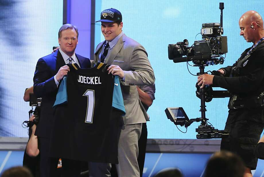 Luke Joeckel, from Texas A&M, stands with NFL Commissioner Roger Goodell after being selected second overall by the Jacksonville Jaguars in the first round of the NFL football draft, Thursday, April 25, 2013, at Radio City Music Hall in New York. (AP Photo/Mary Altaffer) Photo: Mary Altaffer, Associated Press