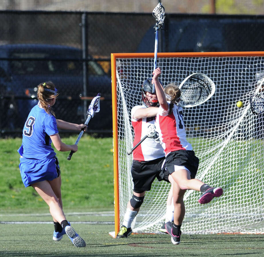 At left, Emily Stein # 9 of Darien shoots and scores in first half action as New Canaan goalie Liz O'Sullivan # 28, center, misses on the stop during the girls high school lacrosse match between New Canaan High School and Darien High School at New Canaan, Thursday, April 25, 2013. Darien won the match, 14-7. Photo: Bob Luckey / Greenwich Time