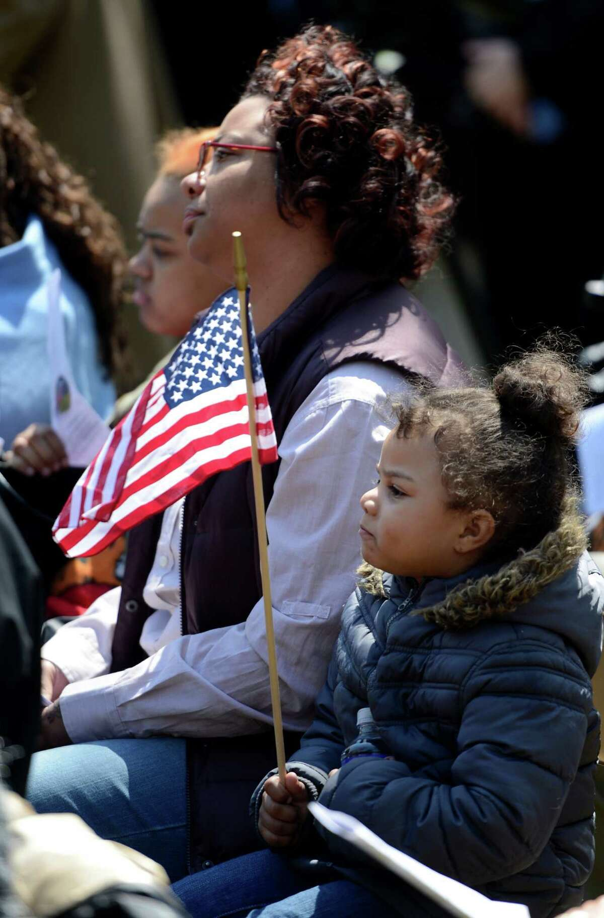 Young Jayla Stalworth, foreground, holds an American flag which will be used to remember a crime victim at the Ceremony of Remembrance held at the Crime Victims Memorial April 25, 2013 in Academy Park in Albany, N.Y. (Skip Dickstein/Times Union)
