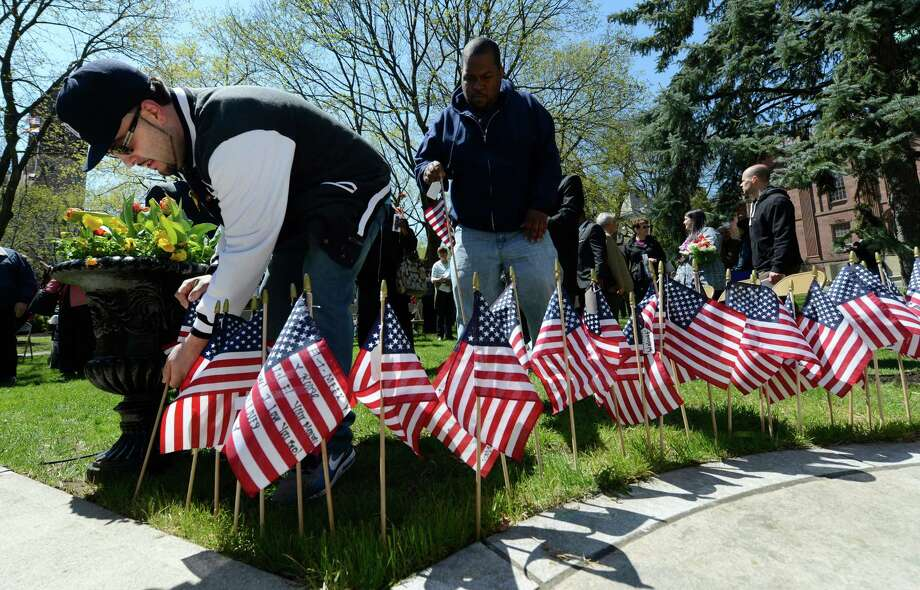 Joe Dunbar, left, places an American flag at the Crime Victims Memorial during the Ceremony of Remembrance April 25, 2013 in Albany, N.Y.  Dunbar's mother Milli was murdered by her husband approximately 10 years ago.  (Skip Dickstein/Times Union) Photo: SKIP DICKSTEIN