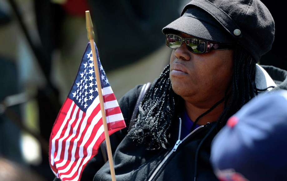 Dorothy Carter of Albany holds an American flag which will be used to remember a crime victim at the Ceremony of Remembrance held at the Crime Victims Memorial April 25, 2013 in Academy Park in Albany, N.Y.   (Skip Dickstein/Times Union) Photo: SKIP DICKSTEIN