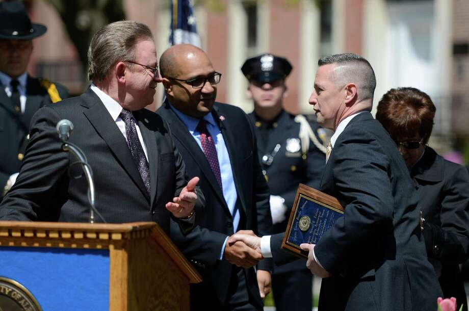 Investigator Christopher R. Smith, right,  of the Colonie Police receives the Infante Outstanding Achievement in Law Enforcement Award from Colonie Police Chief Steve Heider, left, and Albany County DA David Soares, center, at the Ceremony of Remembrance held at the Crime Victims Memorial April 25, 2013 in Academy Park in Albany, N.Y.   (Skip Dickstein/Times Union) Photo: SKIP DICKSTEIN