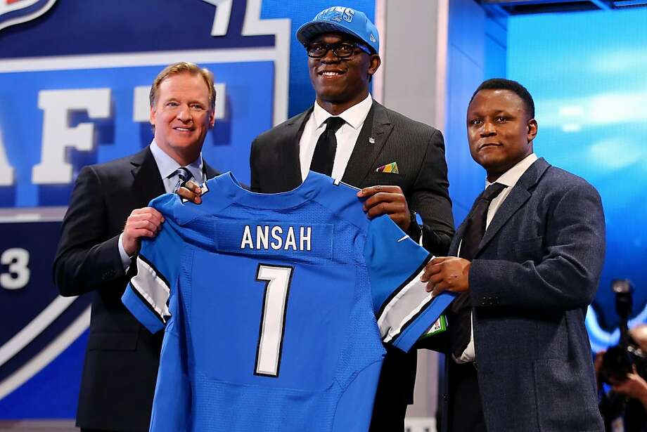 Ezekiel Ansah of the BYU Cougars stands with NFL Commissioner Roger Goodell (L) and Pro Football Hall of Famer Barry Sanders (R) as they hold up a jersey on stage after Ansah was picked #5 overall by the Detroit Lions in the first round of the 2013 NFL Draft at Radio City Music Hall on April 25, 2013 in New York City. Photo: Al Bello, Getty Images
