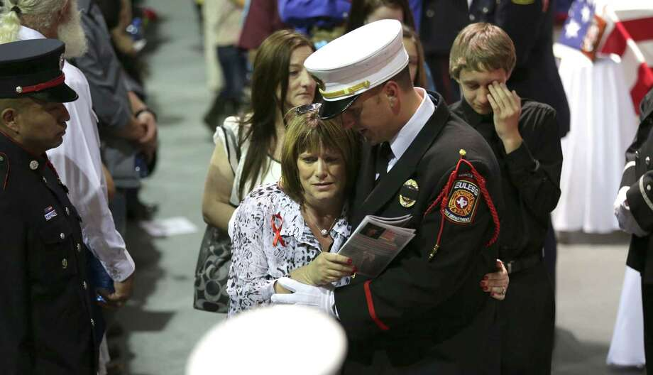 Family members of the fallen firefighter are overcome with grief as the pass the coffins of their loved ones that were killed in the West, TX explosion, on Thursday April 25, 2013 at the Ferrell Center at Baylor University. Photo: Bob Owen, San Antonio Express-News / ©2013 San Antonio Express-News