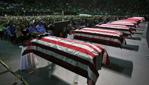 Flag draped coffins line the front of the Ferrell Center at Baylor University on Thursday, April 25, 2013, where President Barack Obama spoke to family members of the first responders that were killed in the explosion in West, TX. Photo: Bob Owen, San Antonio Express-News / ©2013 San Antonio Express-News