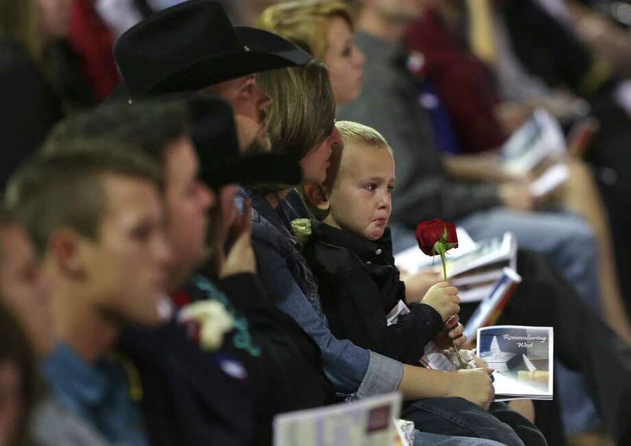 A young boy cries as he holds a red rose in front of his family member's coffin, a fire fighter that was killed in the explosion in West, TX.  The memorial service for the fallen first responders on Thursday, April 25, 2013 was held at the Ferrell Center at Baylor University. Photo: Bob Owen, San Antonio Express-News / ©2013 San Antonio Express-News