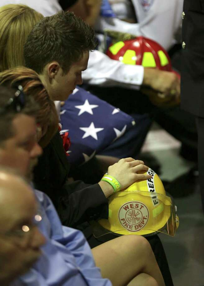 Family members hold flags and helmets of their loved ones that were killed in the explosion in West, TX at a memorial service on Thursday April 25, 2013 at the Ferrell Center at Baylor University. Photo: Bob Owen, San Antonio Express-News / ©2013 San Antonio Express-News
