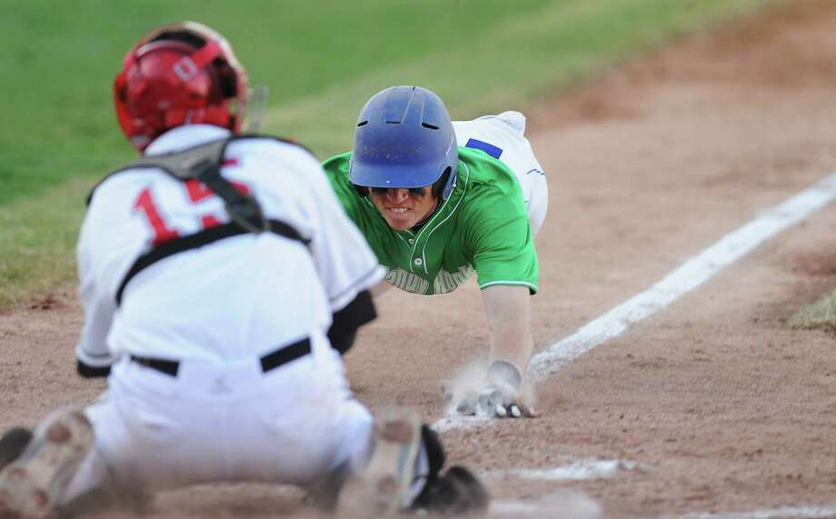 """Newtown's Steven Conway slides into home as Pomperaug catcher Steve Harrison tags him out during Newtown's 5-4 win over Pomperaug in the baseball """"Game to Remember"""" at The Ballpark at Harbor Yard in Bridgeport, Conn. on Thursday, April 25, 2013.  The game was played to honor and acknowledge Sandy Hook Elementary School and the first responders of the December 14 tragedy.  All proceeds benefitted the Sandy Hook Volunteer Fire Department. Photo: Tyler Sizemore / The News-Times"""