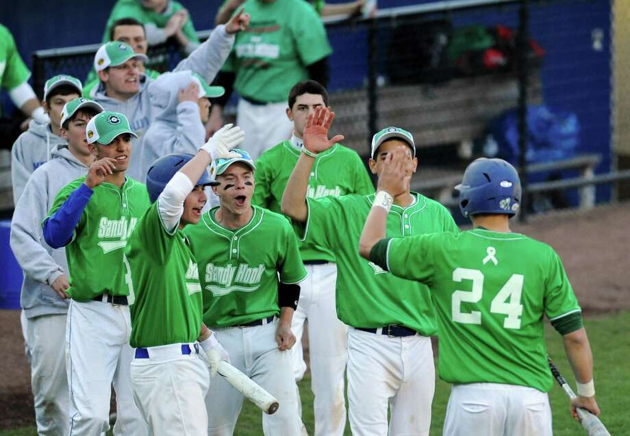 "Newtown's Alex Lapinski (24) is congratulated by teammates after scoring a run in Newtown's 5-4 win over Pomperaug in the baseball ""Game to Remember"" at The Ballpark at Harbor Yard in Bridgeport, Conn. on Thursday, April 25, 2013.  The game was played to honor and acknowledge Sandy Hook Elementary School and the first responders of the December 14 tragedy.  All proceeds benefitted the Sandy Hook Volunteer Fire Department. Photo: Tyler Sizemore / The News-Times"